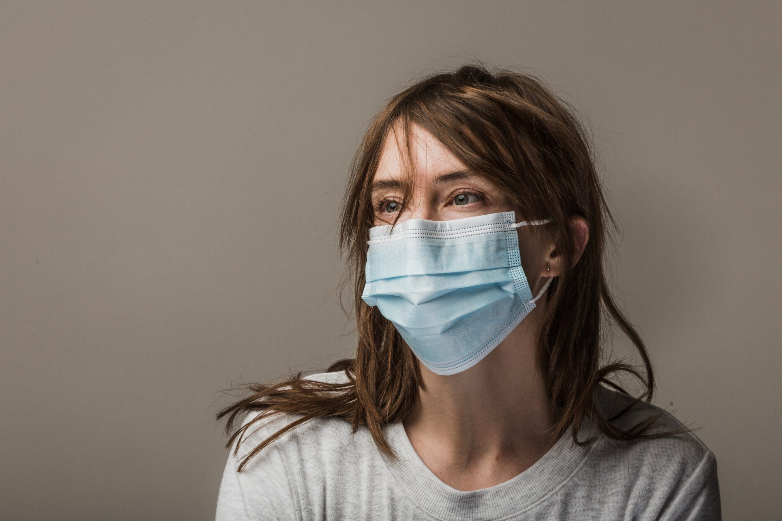 woman-with-brown-hair-wearing-disposable-face-mask